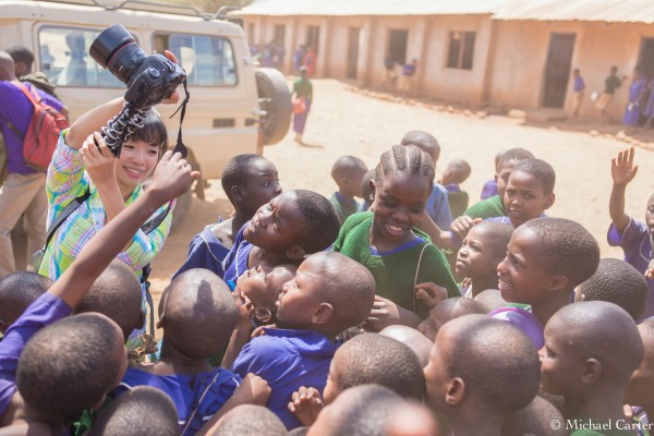 Elley Ho showing Asante Africa students their pictures on the camera screen
