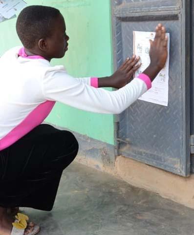 student puting flyer on door